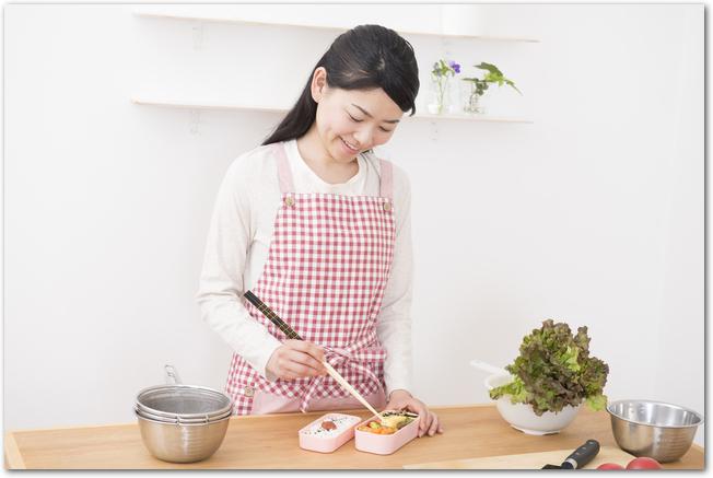 チェックのエプロンをしてお弁当を詰めている女性