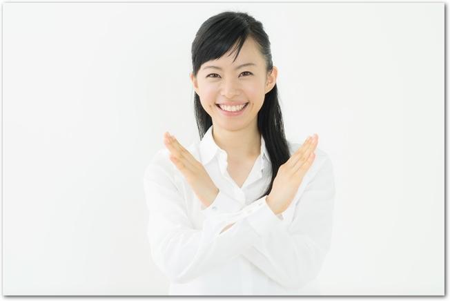 手でバツ印を出す女性
