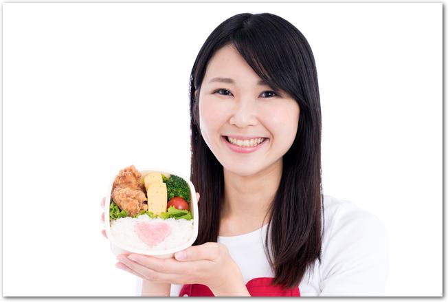 笑顔でお弁当箱の中身を見せる女性