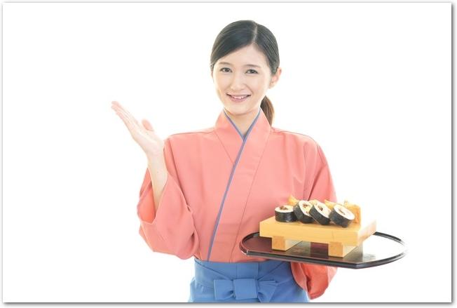 巻き寿司を運んでくる女性