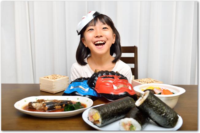 恵方巻きなど節分の食べ物を前に笑っている女の子