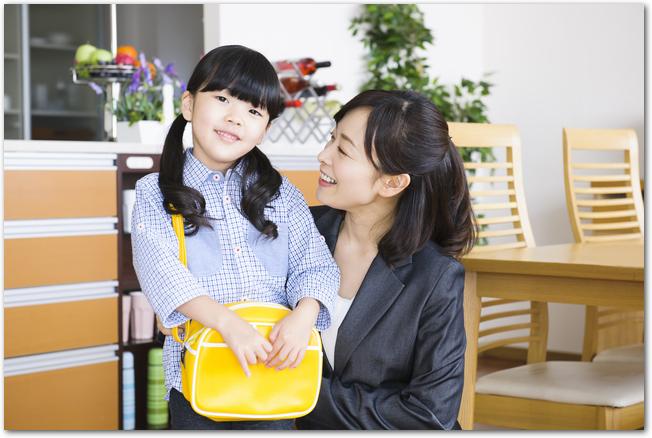 通園バッグをかける女の子とお母さん
