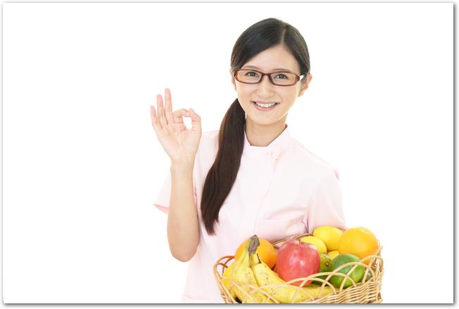 フルーツたっぷりの籠を抱える女性
