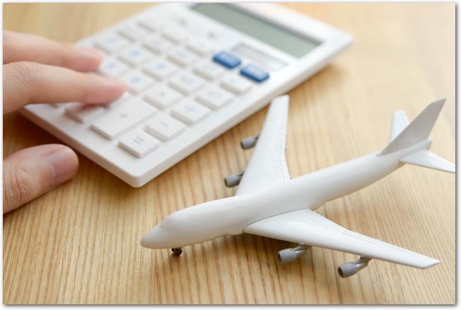 飛行機の模型と計算機、旅行先は海外か国内か