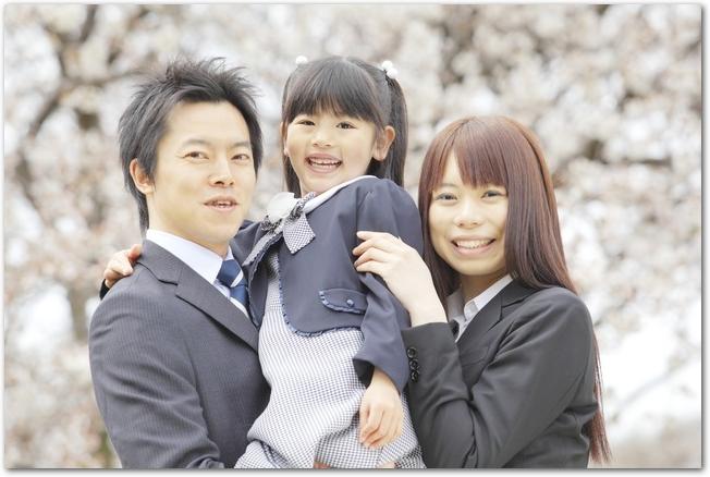 桜並木を歩くパパ・ママ・女の子