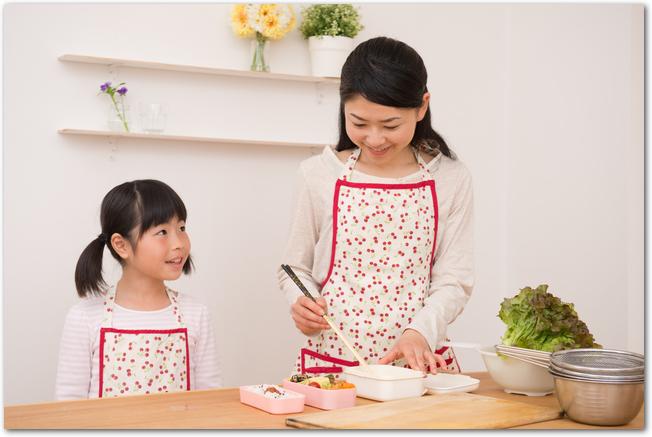 お弁当を作っているママと女の子