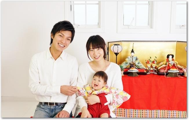 ひな飾りの前に並ぶパパママと赤ちゃん