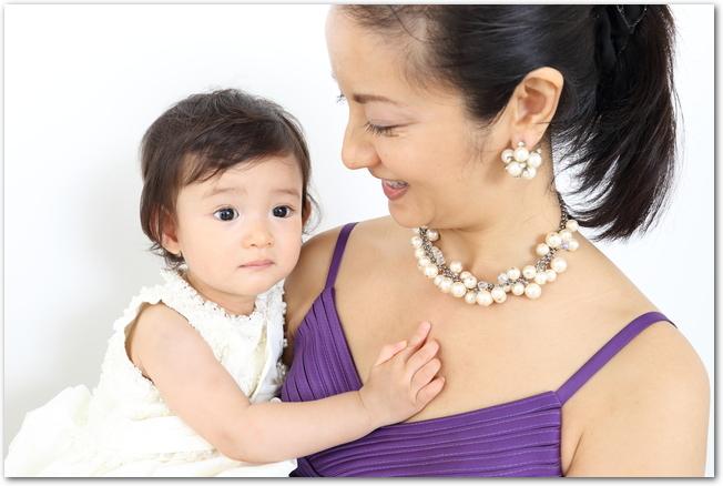 結婚式に出席するためにドレスを着ているママと女の赤ちゃん