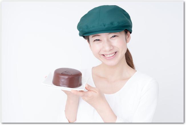 手作りのチョコレートケーキを手に持った女性