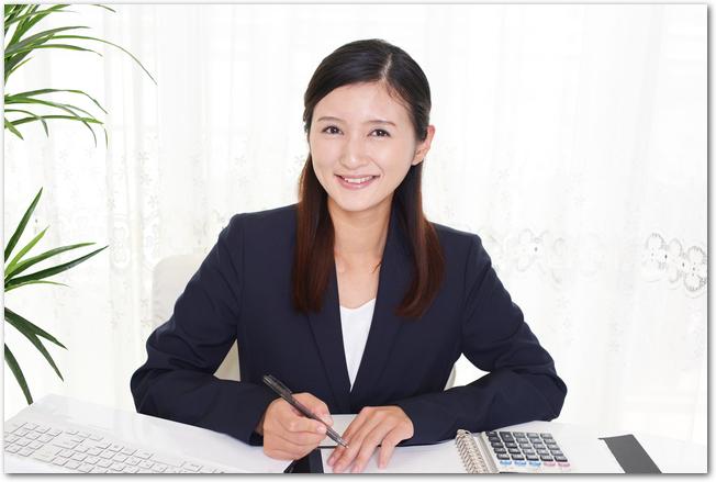 パソコンに向かい電卓をたたき事務処理をする女性