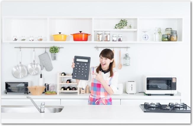 キッチンから節約を目指して電卓をたたく女性