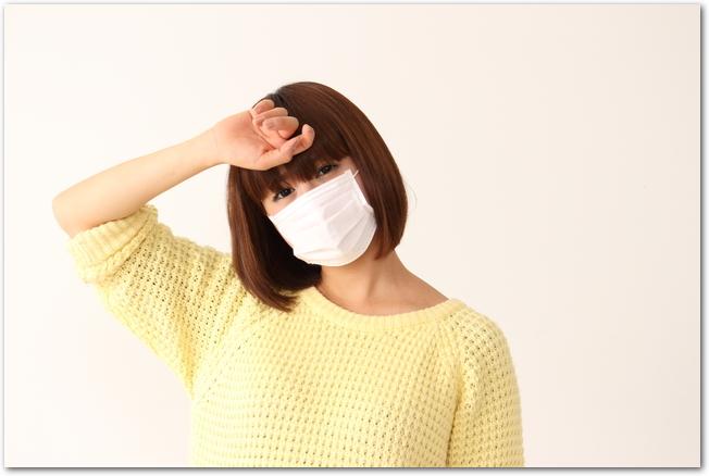 花粉症でマスクをしていて頭痛にも悩まされている女性