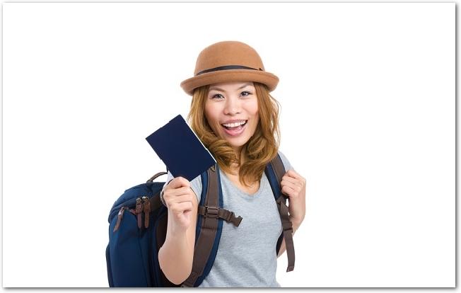 パスポートを手に持ちアジア旅行に出かける女性