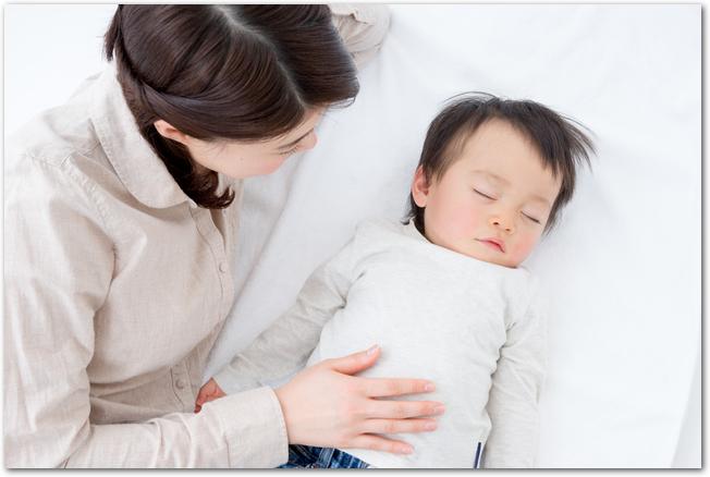 寝ている赤ちゃんと添い寝するママ