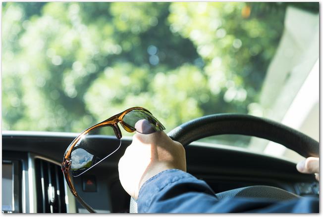ドライブをしながらサングラスを手に持つようす