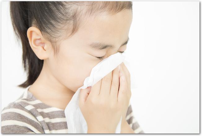 花粉症で鼻をかむ女の子
