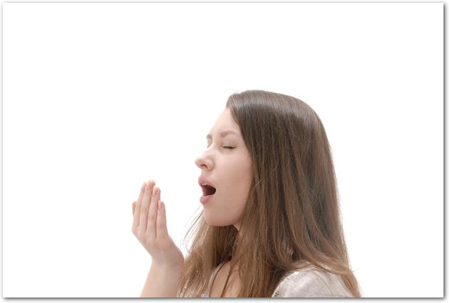 花粉症で眠くてあくびをしている女性