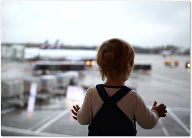 空港で飛行機を見ている赤ちゃん
