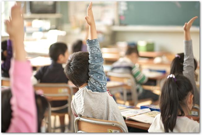 授業参加日に元気よく手を挙げている男の子