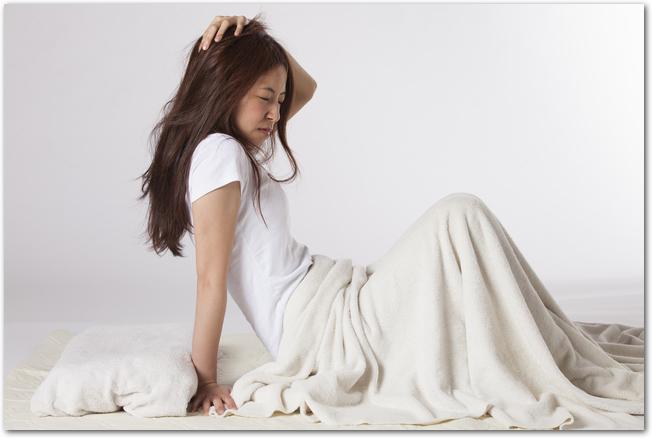 梅雨時の食中毒で体調がよくなくて横になっている女性
