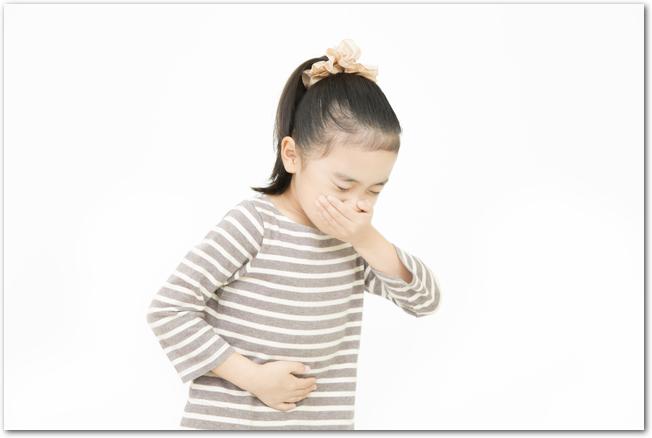 食中毒と思われる症状でお腹を押さえる女の子