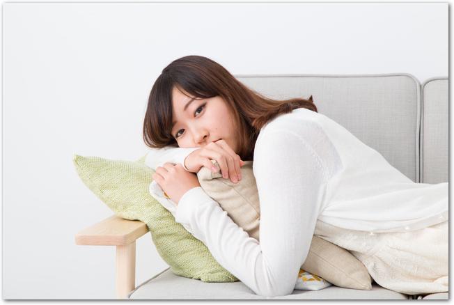 体がだるくソファーに横たわる女性