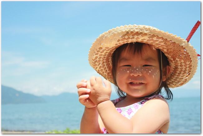 日焼け対策の麦わら帽子をかぶる赤ちゃん