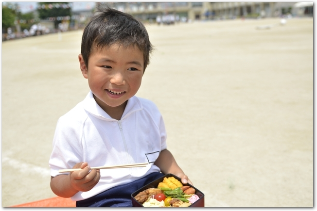 運動会のお昼ごはんにお弁当を食べる男の子