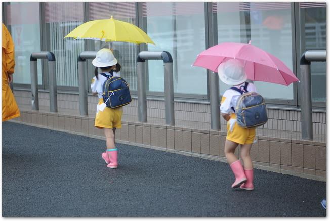 傘をさして長靴を履いて登園する子どもたち