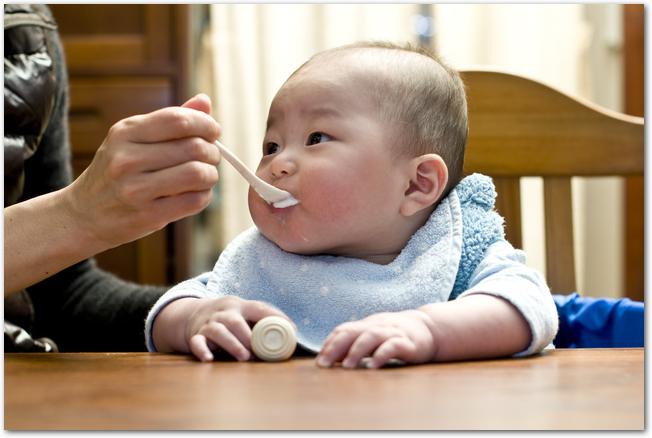 ママに離乳食を食べさせてもらっている赤ちゃん
