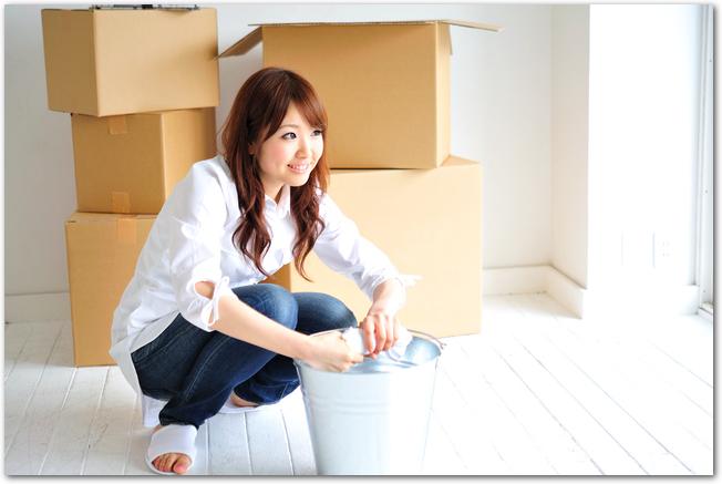 引越し荷物をまとめながら掃除する女性