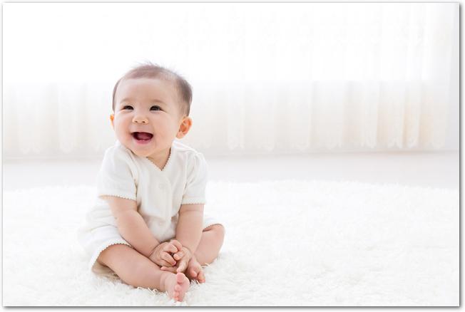 日当たりのよい部屋に座り笑っている赤ちゃん