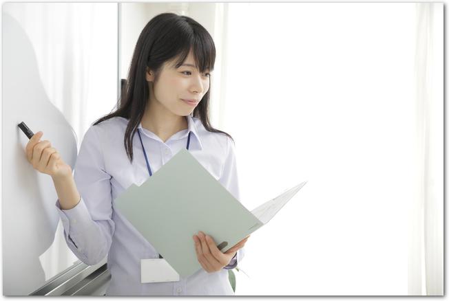 便箋とペンを手に持ち挨拶文をつくろうとしている女性