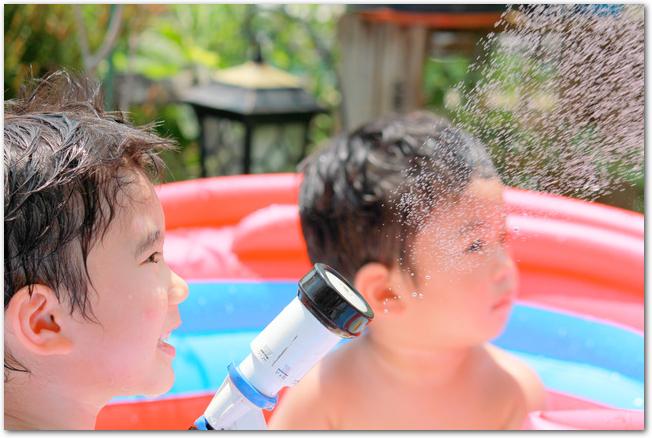 プールサイドでホースで水まきをして楽しそうな男の子