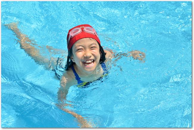 日焼け止めをして外のプールで遊ぶ女の子