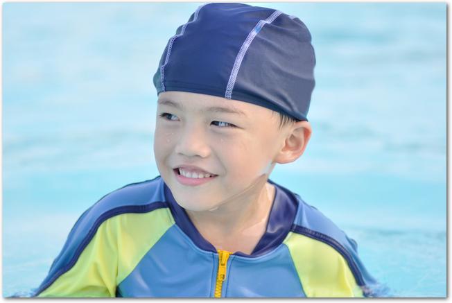 プールに入って笑顔の男の子
