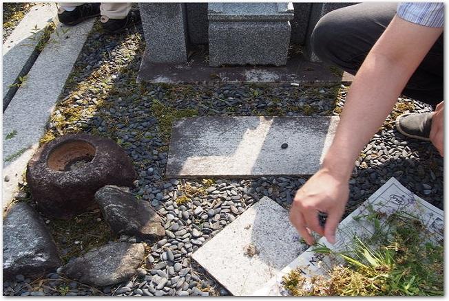 お墓の周りを掃除するようす