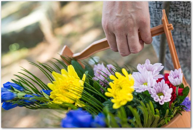 お花をもってお墓参りに向かう女性