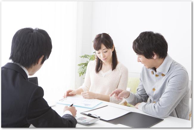 スーツ姿のビジネスマンと保険の話をする夫婦