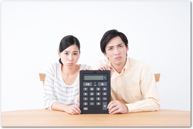 テーブルに座って大きな電卓を持つ若い夫婦