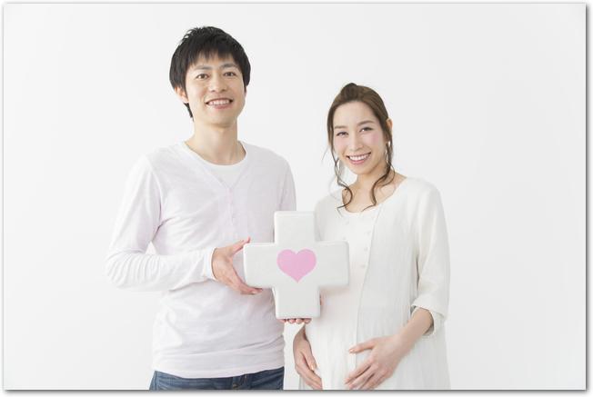 ハートが描かれた白い十字を持つ夫婦