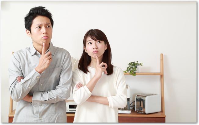 上を見て悩む表情をする若い夫婦