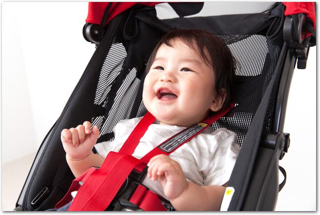 ベビーカーに乗っている笑顔の赤ちゃん