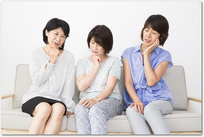 ソファーに並んで座って首をかしげる3人の50代女性
