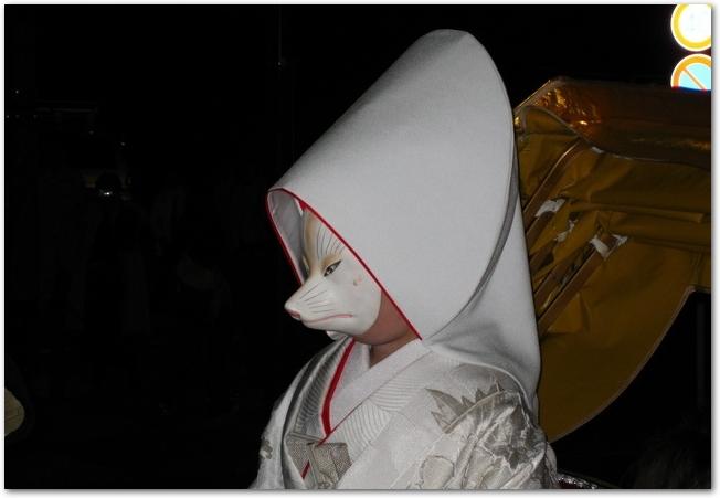 狐の嫁入り行列の狐のお面をつけた白無垢姿の花嫁