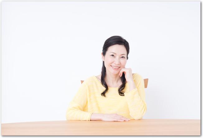 椅子に座って微笑んでいる50代女性