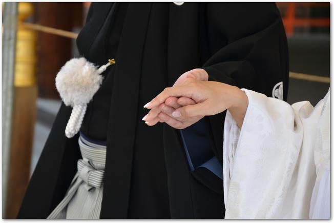 白無垢姿の新婦の右手を取る和装の新郎の左手