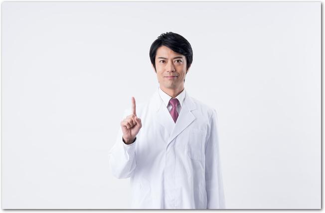 指をさす白衣姿の男性医師