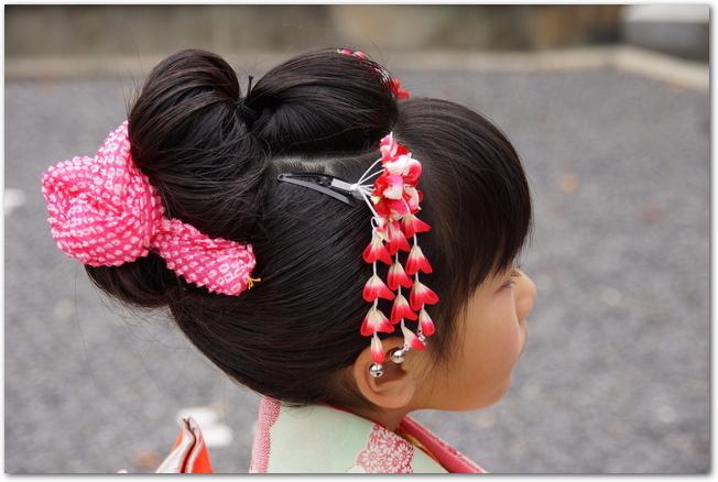 髪をアップにして髪飾りをつけた七五三の女の子の後ろ姿