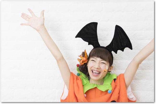 ハロウィンの仮装をしてバンザイをする女性